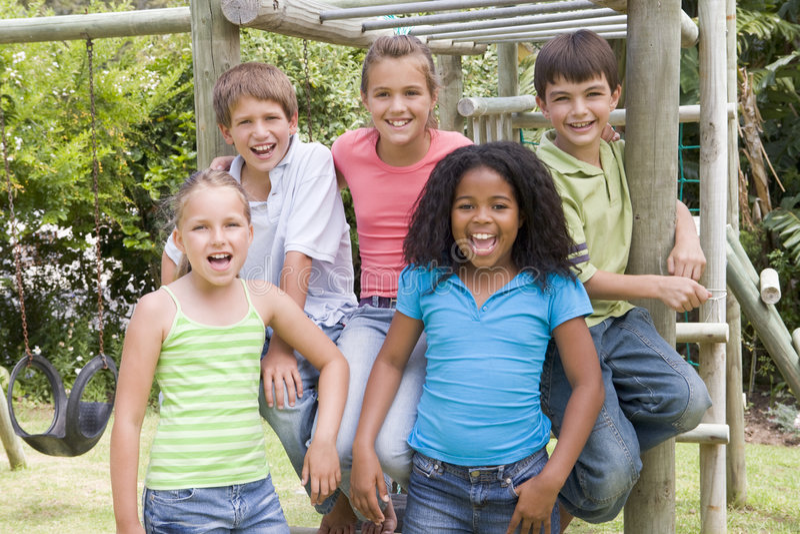 Fünf junge Freunde an einem Spielplatzlächeln stockfoto