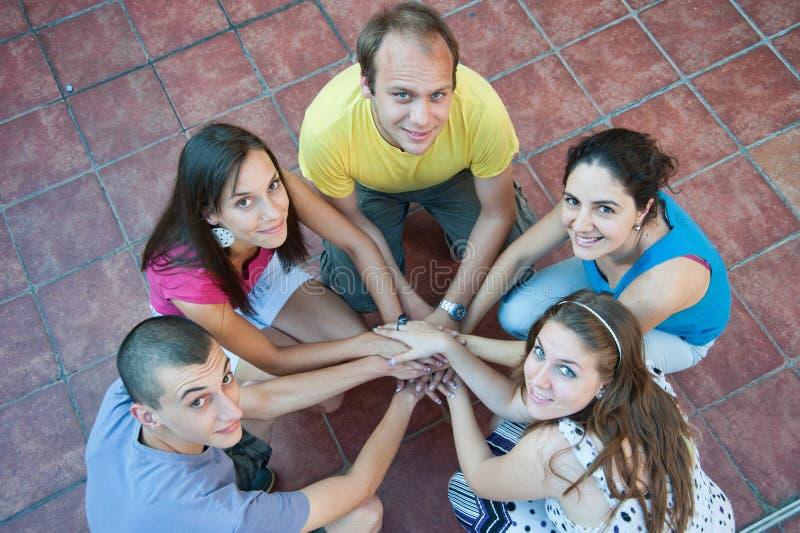 Fünf junge Leute in einem Kreis lizenzfreies stockbild