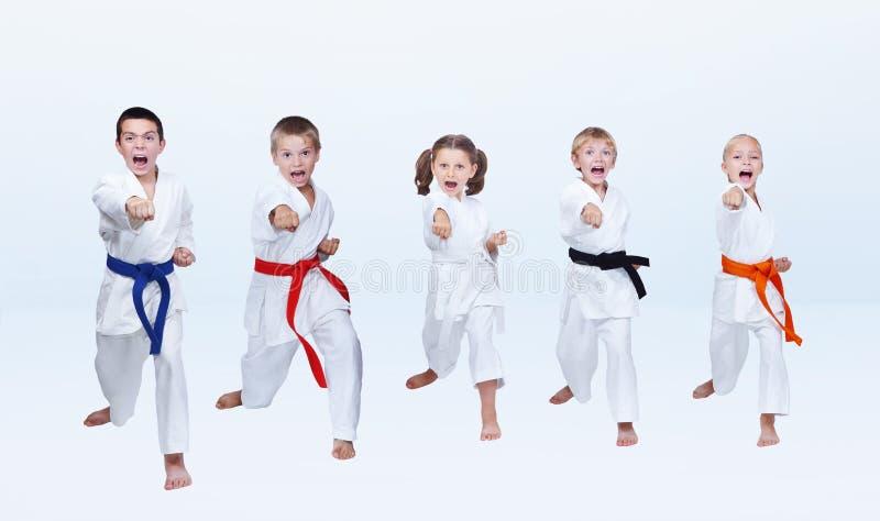 Fünf karateka Kinder schlagen Durchschlagsarm stockbilder