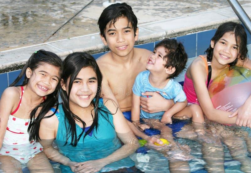 Fünf Kinder, die im Pool sitzen lizenzfreies stockbild