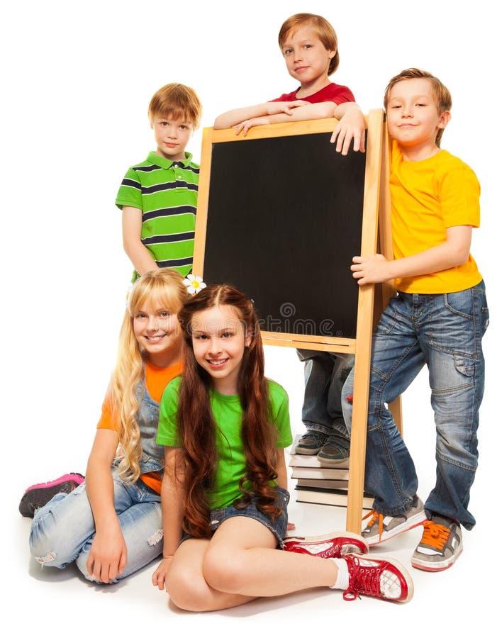 Fünf Kinder mit Tafel lizenzfreies stockbild