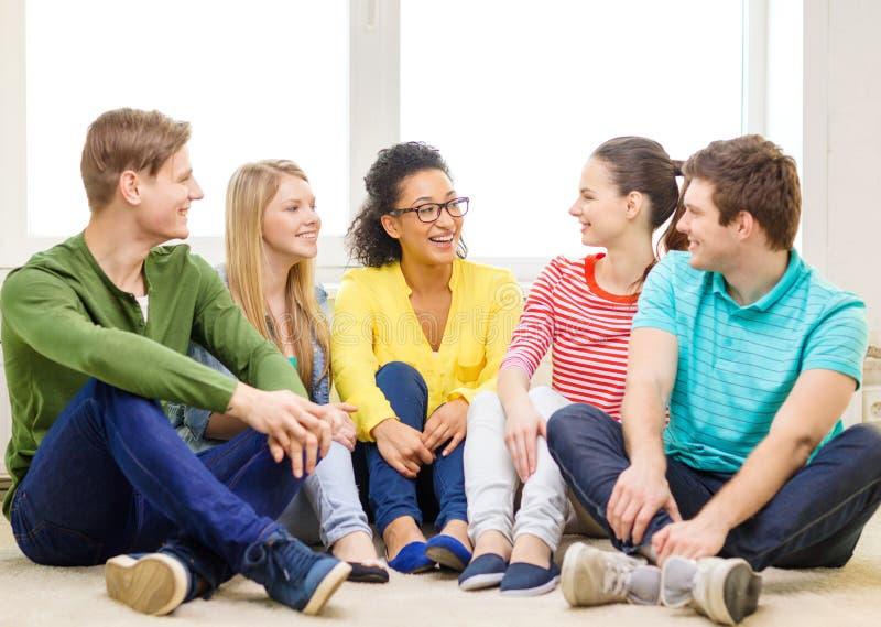 Fünf lächelnde Jugendliche, die Spaß zu Hause haben stockfotografie