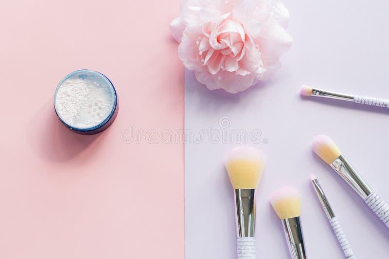 Fünf Make-upbürsten mit Beschriftung auf dem Griff und dem Mineralpulver in einem blauen Glas, Haarklemme stockbild