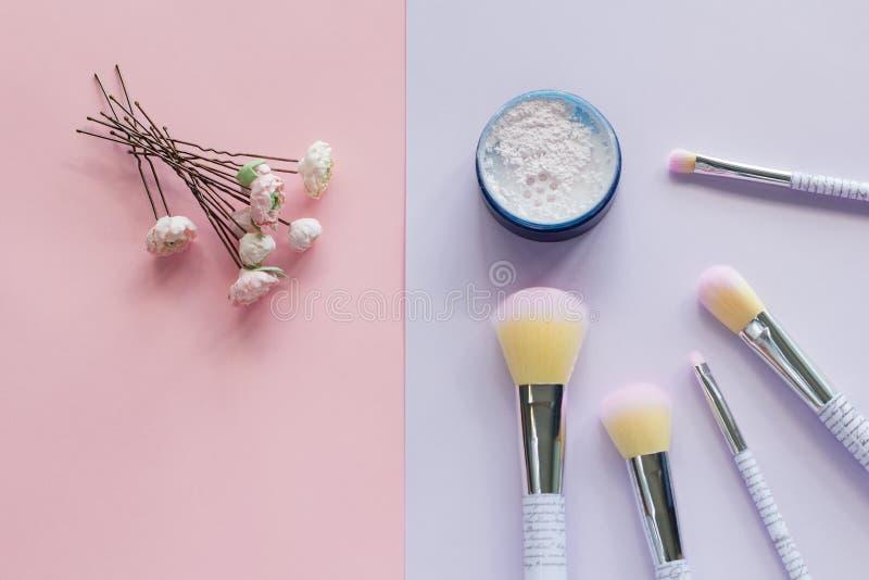 Fünf Make-upbürsten mit Beschriftung auf dem Griff und dem Mineralpulver in einem blauen Glas, Heiratshaarnadeln lizenzfreie stockfotos
