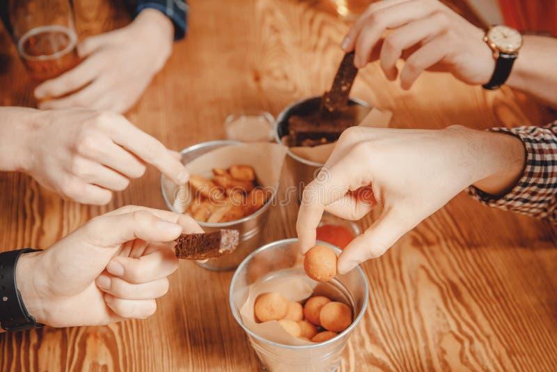 Fünf Mannhände nah oben, Bierimbisse an der Bar halten und essen Käse boals, Chipland patatoes lizenzfreie stockfotografie