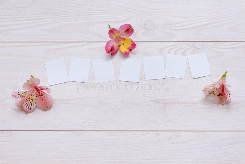 Fünf Papiere für fünf Buchstaben auf dem hölzernen Hintergrund mit Blumen stockfotos