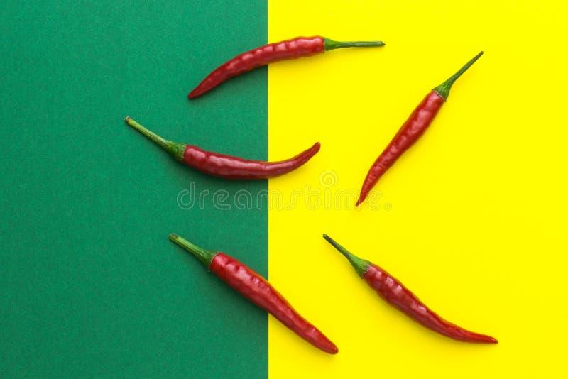 Fünf Pfeffer des roten Paprikas auf einem gelbgrünen Hintergrund stockfotos