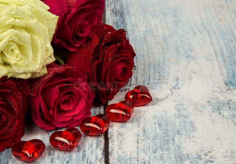 Fünf Rosen und rote Herzen auf einem Hintergrund einer hölzernen Tischplatte I stockfotografie