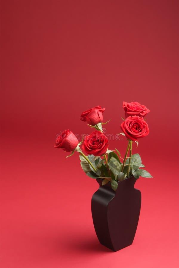 Fünf rote Rosen im Vase auf dem roten Hintergrund lizenzfreie stockbilder