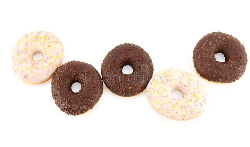 Fünf süße Weiß- und Schokoladenschaumgummiringe lokalisiert lizenzfreie stockbilder
