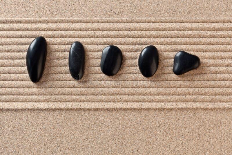 Fünf schwarze Kiesel auf geharktem Sand stockfotografie