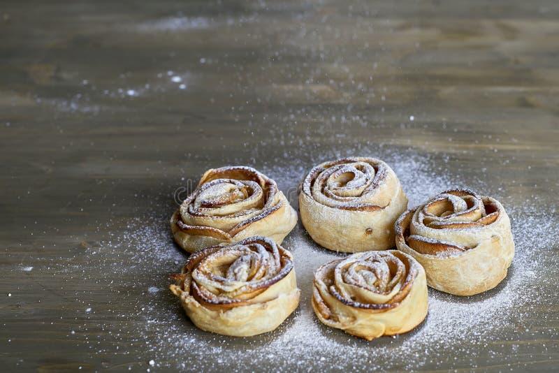 Fünf Stücke, die köstlich sind und Bonbon gebackene Rose formten Gebäck mit Apfelfüllung auf dem hölzernen Hintergrund, der mit G lizenzfreie stockbilder