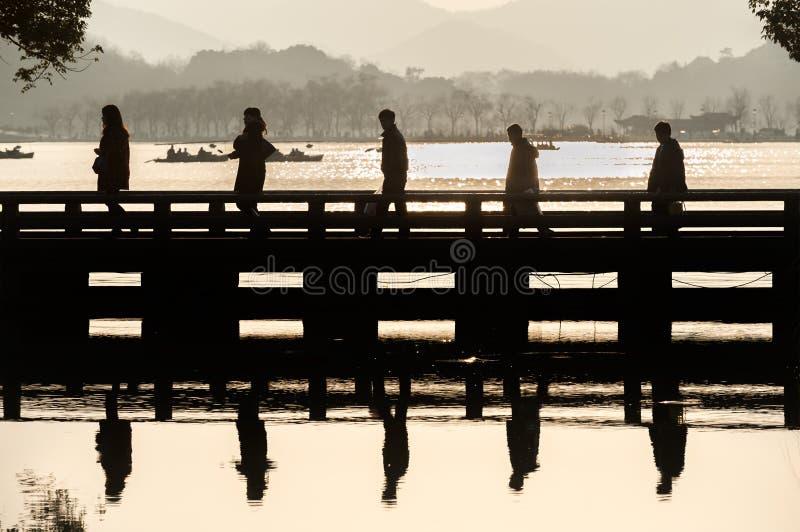 Fünf Touristen im Schattenbild kreuzen eine Brücke an Hangzhou-` s Westsee Naturschutzgebiet stockfoto