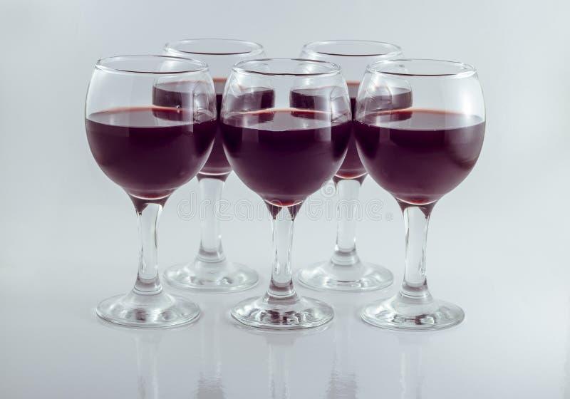 Fünf transparente Glasgläser Rotwein der Traube stockfotografie