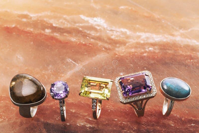 Fünf verschiedene Goldringe mit Edelsteinen auf einer Marmoroberfläche lizenzfreie stockfotografie
