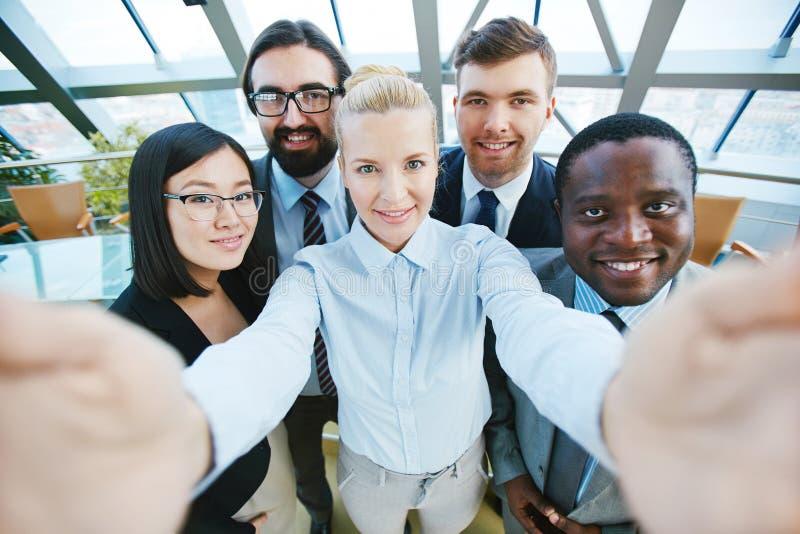 Fünf verschiedene Teammitglieder, welche die Kamera beim Lächeln über ihren Erfolg betrachten stockbilder