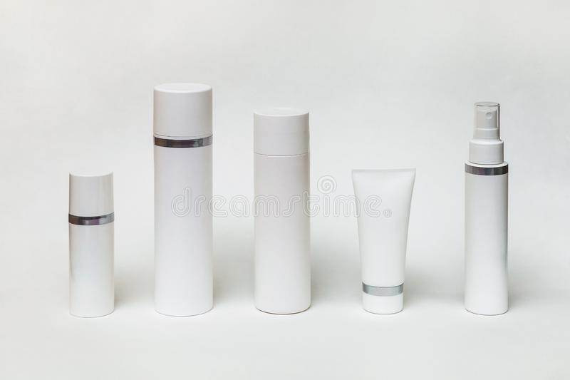 Fünf verschiedene weiße Flaschen und Rohre für Kosmetik lizenzfreie stockbilder