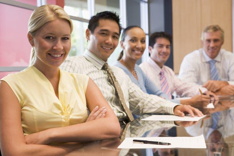 Fünf Wirtschaftler am Sitzungssaaltabellenlächeln stockfotografie
