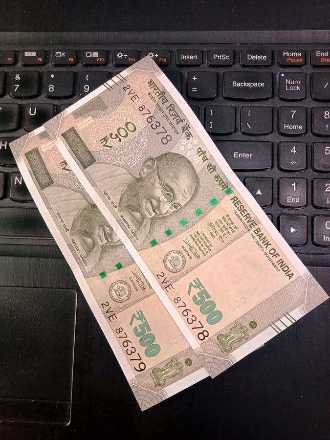 Fünfhundert Rupien indische Banknoten über eine Laptoptastatur lizenzfreie stockfotos