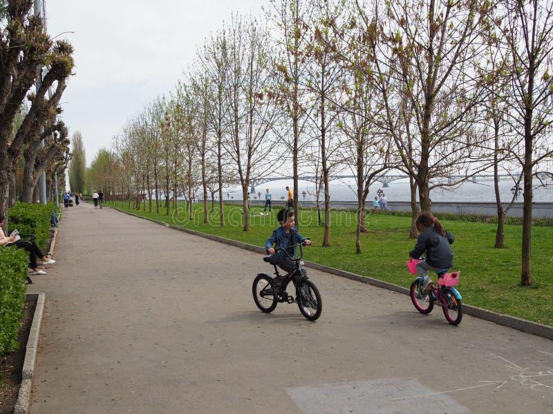 Fünfjährige Kinder Junge und Reitenfahrräder des Mädchens Das Konzept der Freundschaft Russland, Saratow - 28. April 2019 stockfotos