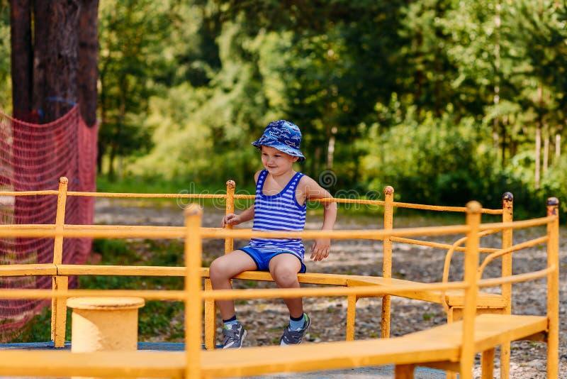 Fünfjähriger lächelnder kaukasischer Junge in einem Hut Karussell der Reitenein große Kinder im Park lizenzfreies stockfoto