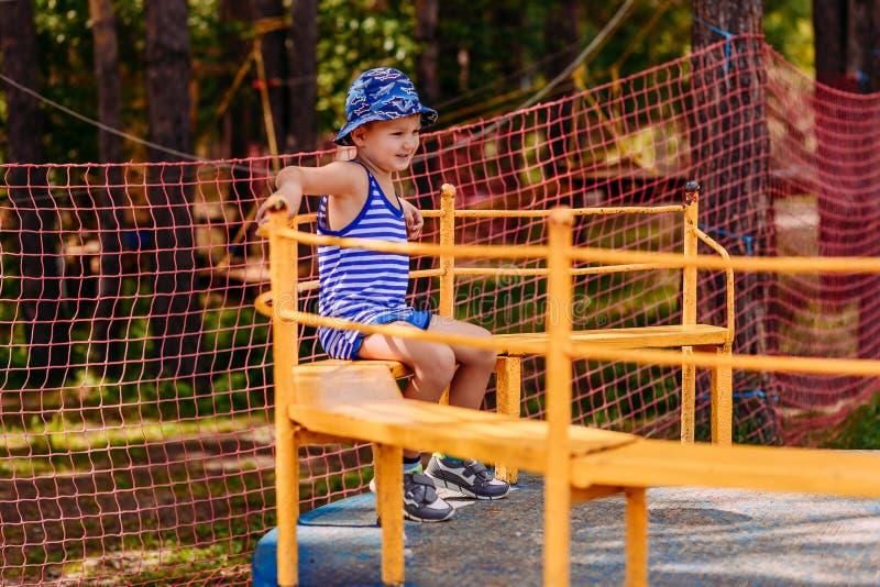 F?nfj?hriger l?chelnder kaukasischer Junge in einem Hut Karussell der Reitenein gro?e Kinder in einem Sommer Park stockfoto