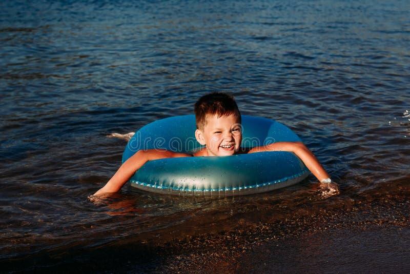 Fünfjähriges lächelndes Kinderschwimmen im Meer lizenzfreie stockfotografie