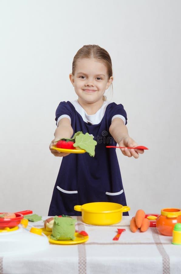 Fünfjahreshosteß bietet Platte des Lebensmittels und des Löffels an lizenzfreie stockbilder