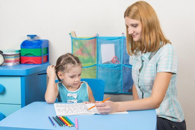 Fünfjahresmädchen zeichnet den Bleistift in einem Notizbuch und den Rahmen untersucht stockbild