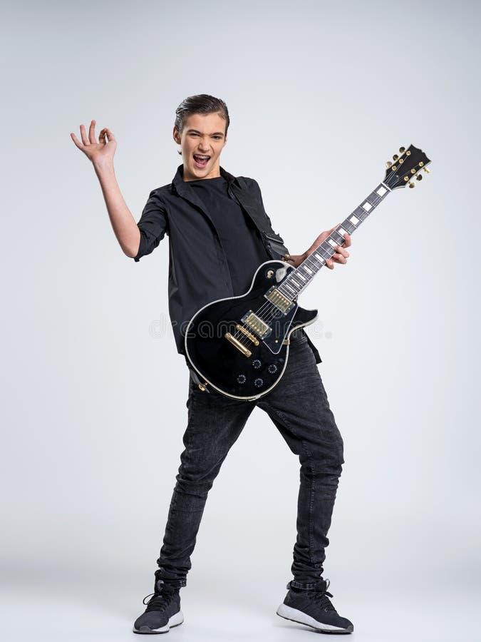 Fünfzehn Jahre alte Gitarrist mit einer schwarzen E-Gitarre Jugendmusiker hält Gitarre lizenzfreies stockbild