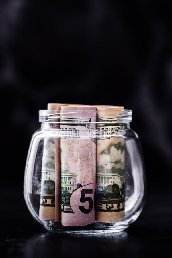 Fünfzig Dollar-Banknoten gerollt oben in der Glasflasche stockbilder