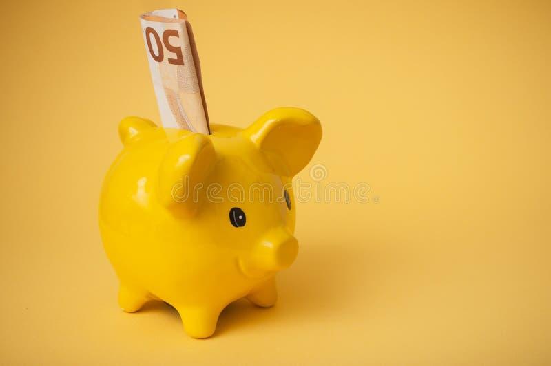 fünfzig-Euro-Banknote im gelben Sparschwein auf gelbem Hintergrund lizenzfreies stockbild
