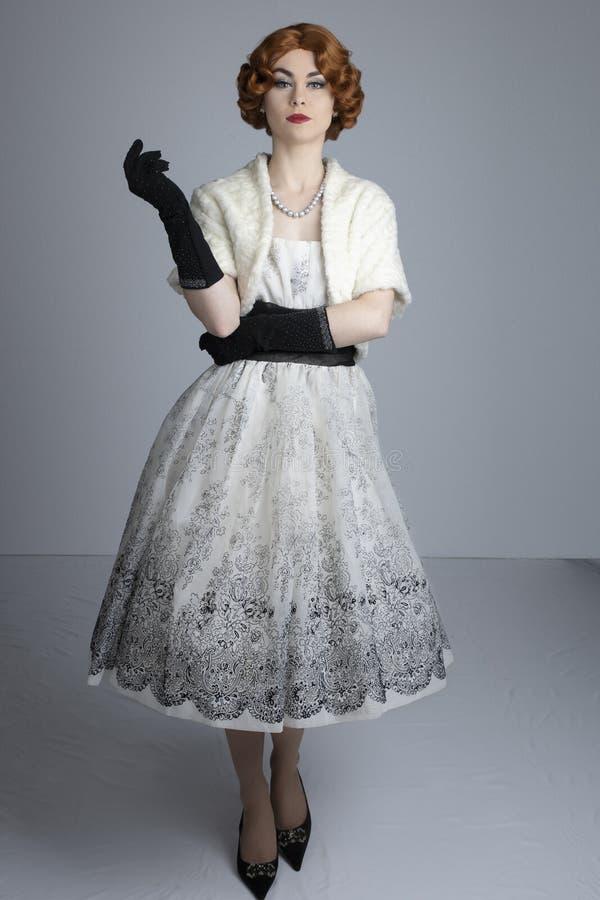 fünfziger Jahre Frau im Schwarzweiss-Kleid, das eine Pelzstola trägt stockfotografie