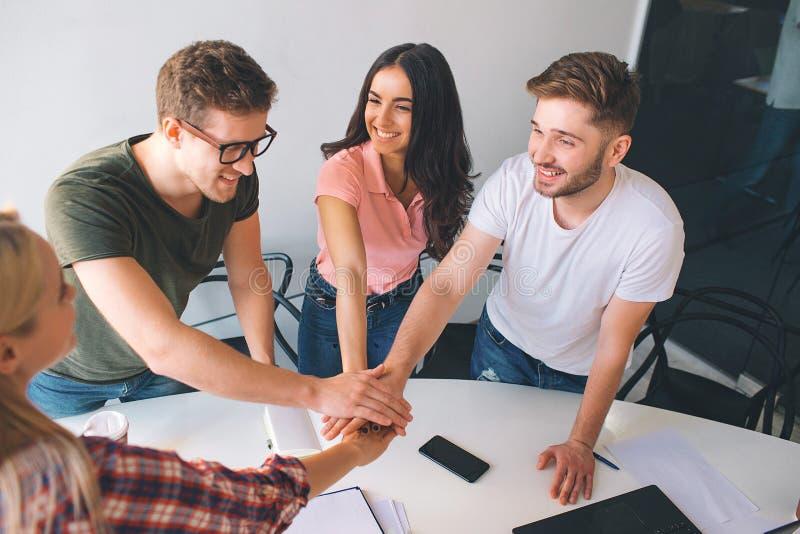 Für die netten und glücklichen Mitarbeiter stehen Sie um weiße Tabelle und betrachten Sie einander Sie halten Hände zusammen Leut stockfotos