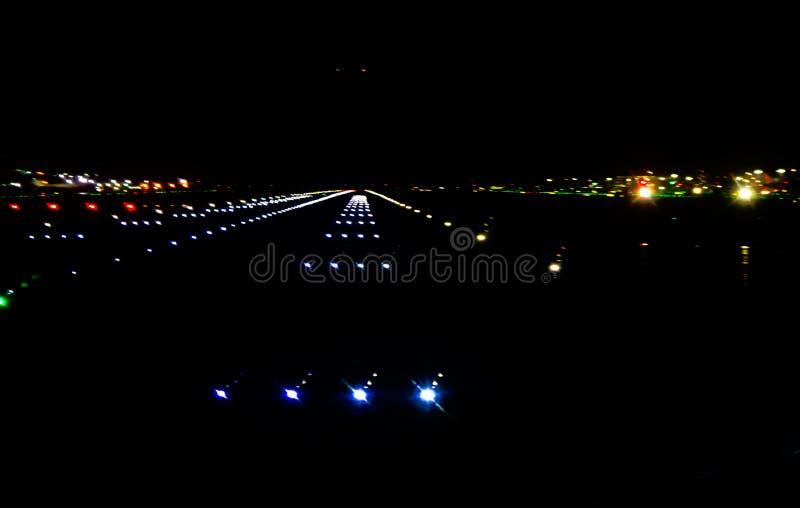 Für eine Landung hereinkommen - abstrakter Flughafen runnway in der Dunkelheit auf einem nassen Nacht-backgound lizenzfreies stockfoto