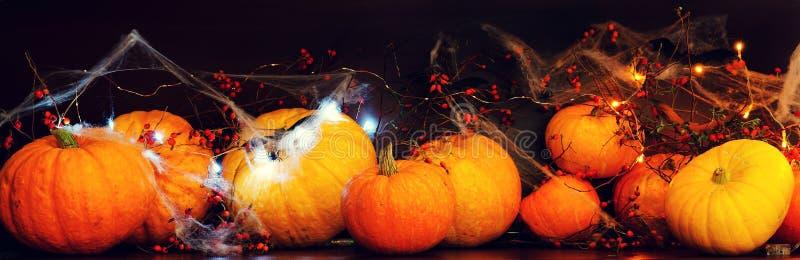 Für Halloween, Reinigung und schnitzen Gesichter von den Kürbisen, von den Kürbisen auf einer dunklen Tabelle mit Spinnennetzen u lizenzfreies stockbild