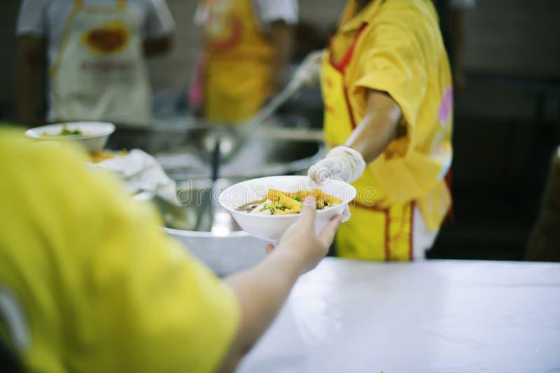 Für Mitmenschen in der Gesellschaft durch das Geben der Nahrung sich interessieren, gebend ohne Hoffnung: Das Konzept der schlech stockfotografie