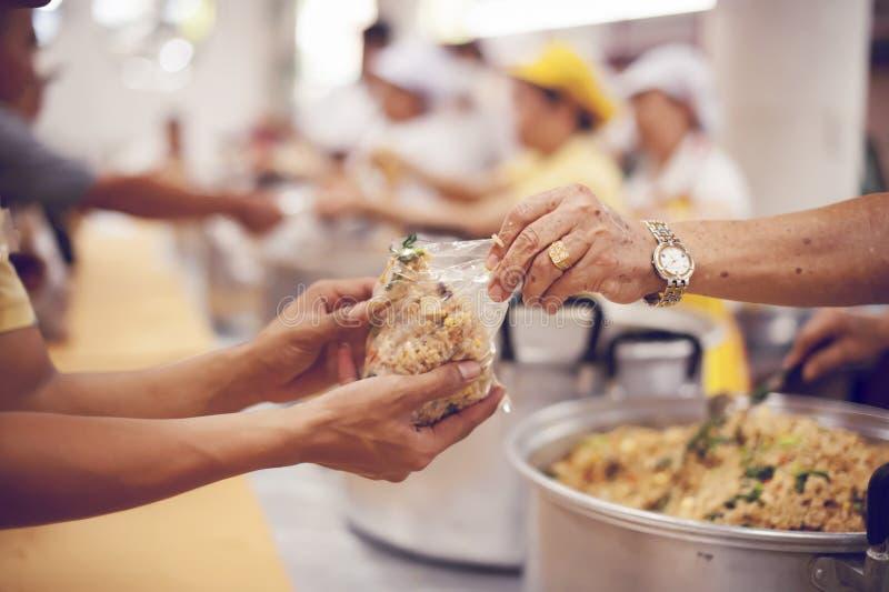 Für Mitmenschen in der Gesellschaft durch das Geben der Nahrung sich interessieren, gebend ohne Hoffnung: Das Konzept der schlech lizenzfreie stockbilder