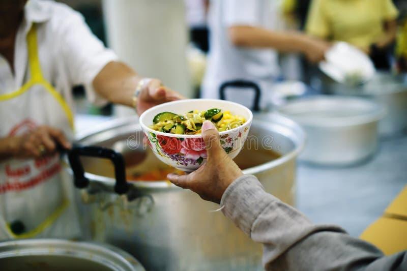 Für Mitmenschen in der Gesellschaft durch das Geben der Nahrung sich interessieren, gebend ohne Hoffnung: Das Konzept der schlech stockfoto