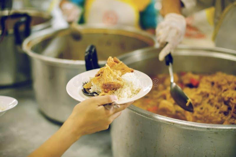 Für Mitmenschen in der Gesellschaft durch das Geben der Nahrung sich interessieren, gebend ohne Hoffnung: Das Konzept der schlech stockfotos