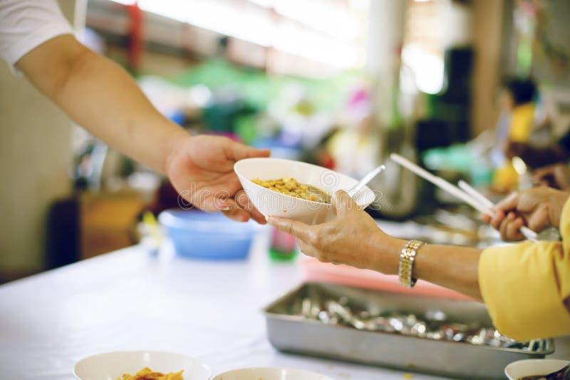 Für Mitmenschen in der Gesellschaft durch das Geben der Nahrung sich interessieren, gebend ohne Hoffnung: Das Konzept der schlech stockbild