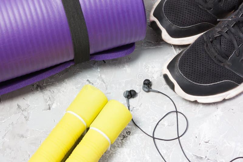 Für Sport sich vorbereiten, gesunder Lebensstil, Turnschuhe, Dummköpfe, Seilspringen, Yogamatte stockfotografie