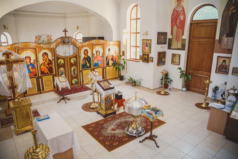 Für Taufe in der Kirche sich vorbereiten, Innendraufsicht der Kirche, goldene religiöse Geräte: Bibel, Kreuz, Gebetsbuch, Tauf- stockbilder