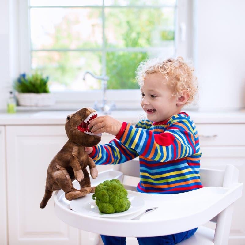 Fütterungsbrokkoli des kleinen Jungen zum Spielzeugdinosaurier lizenzfreies stockbild