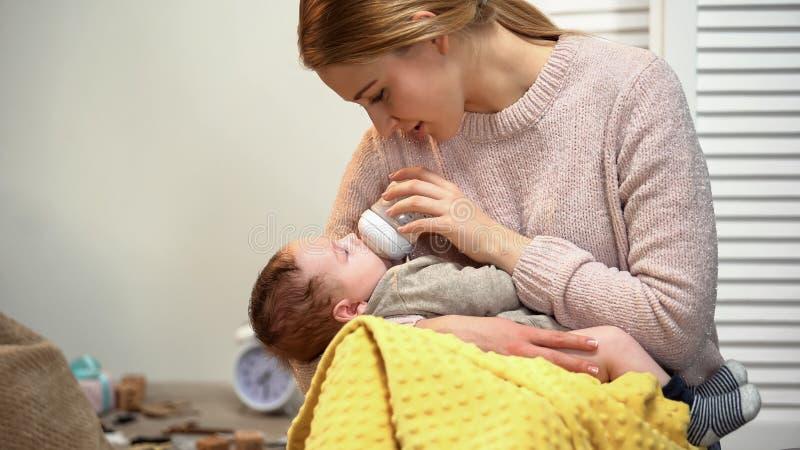 Fütterungskind der jungen Mutter von der Flasche, Probleme mit Stillen, Brustdrüsenentzündung stockfotografie
