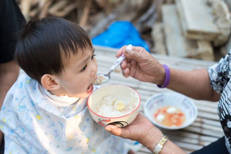 Fütterungslebensmittel des asiatischen Babys durch Großmutter lizenzfreie stockfotografie
