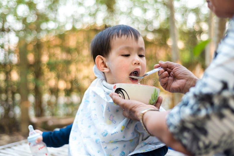 Fütterungslebensmittel des asiatischen Babys durch Großmutter lizenzfreies stockfoto