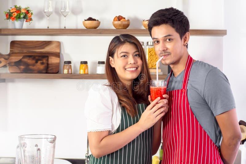 Fütterungssmoothie erdbeere der hübschen Frau zu ihrem Freund lizenzfreies stockfoto