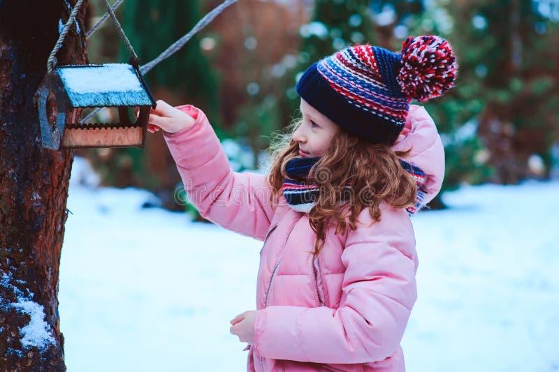 Fütterungsvögel des Kindermädchens im Winter Vogelzufuhr im schneebedeckten Garten, helfende Vögel während der kalten Jahreszeit stockbild