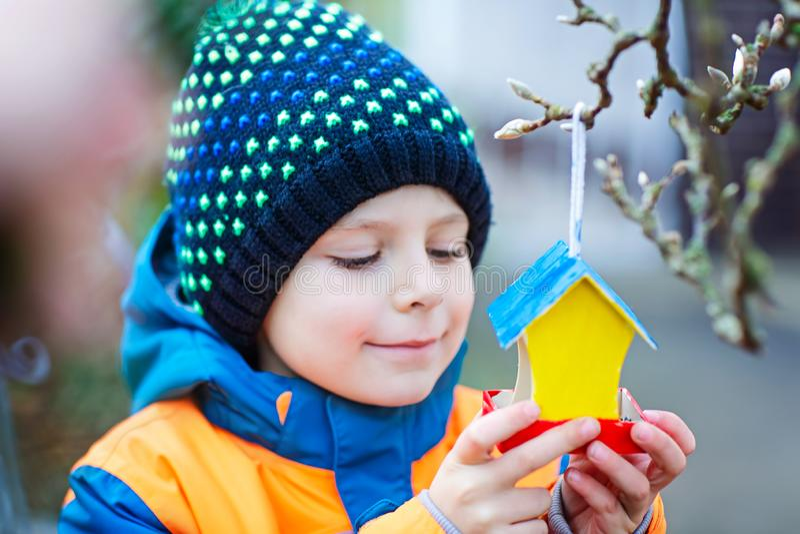Fütterungsvögel des Kleinkindjungen im Winter Kind, das buntes selbst gemachtes Vogelhaus auf Baum am eisigen kalten Tag hängt gl stockfotografie